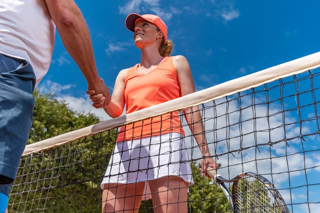 Stringe la mano in rete sul torneo di tennis.