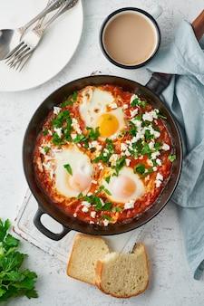Shakshouka, uova in camicia in salsa di pomodori, olio d'oliva. cucina mediterranea.