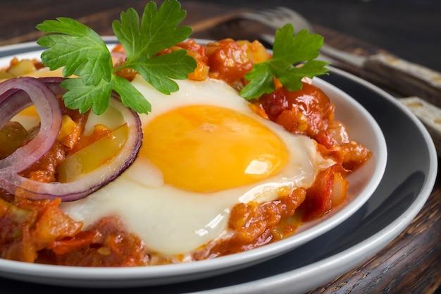 Shakshuka, un piatto tradizionale israeliano. uovo soleggiato con pomodori in umido.