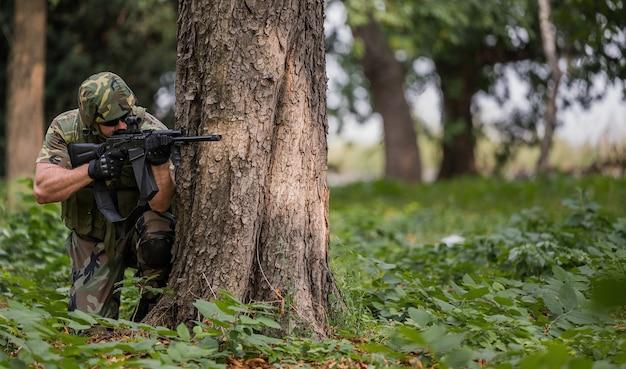 Colpo poco profondo del fuoco di un soldato in un ambiente naturale