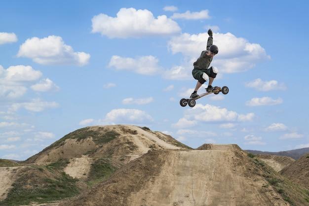 Messa a fuoco poco profonda di un giovane ragazzo che fa skateboard su una pista sterrata