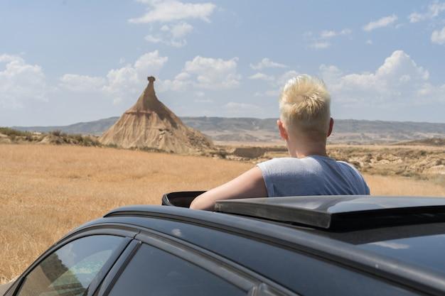 Messa a fuoco poco profonda di un giovane maschio caucasico in un'auto nera nel campo