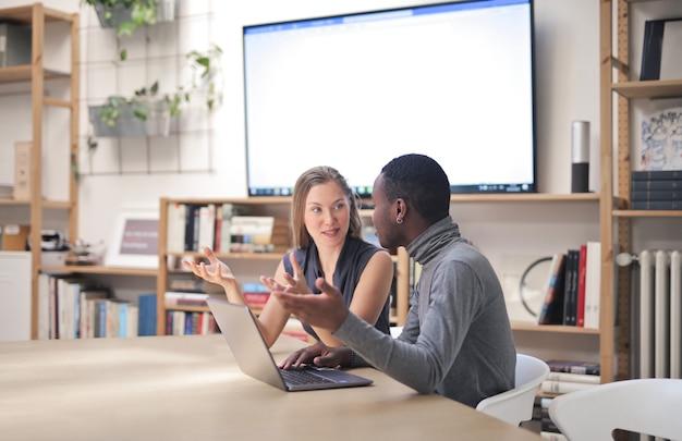 Messa a fuoco poco profonda di giovani che lavorano insieme in un ufficio moderno