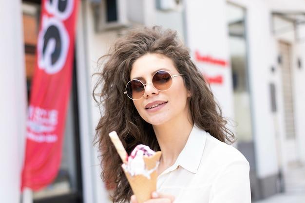 Fuoco poco profondo di una giovane donna che tiene un cono gelato all'aperto