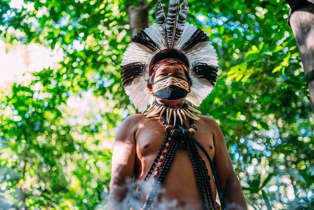Sciamano della tribù dei pataxã³. anziano uomo indiano che indossa un copricapo di piume e una maschera per il viso a causa della pandemia covid-19
