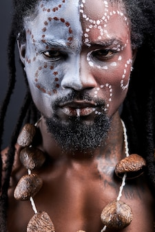 Uomo rituale tribale sciamano isolato in studio, aborigeno esotico con trucco etnico sul viso, maschio africano senza camicia con i dreadlocks