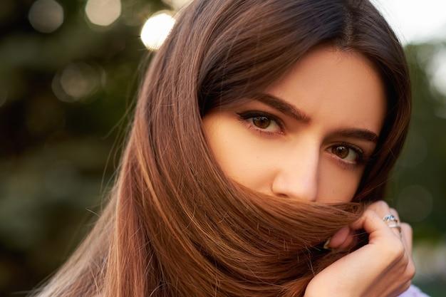 Espressione facciale di vergogna e timidezza. la ragazza timida nasconde il viso