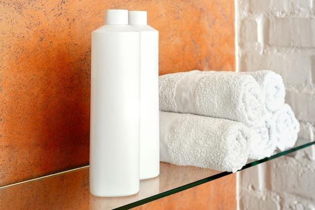Shampoo balsamo sapone bottiglia di prodotto cosmetico per la cura dei capelli, igiene del corpo e rotoli di asciugamani bianchi sulla mensola del bagno.
