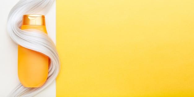 Bottiglia di shampoo avvolto in ciocca di capelli biondi su sfondo di colore arancione. shampoo bottiglia d'oro in ciocca di capelli tinti. spazio della copia vista dall'alto. cosmetici per la cura dei capelli prodotti di bellezza per il bagno trattamento dei capelli