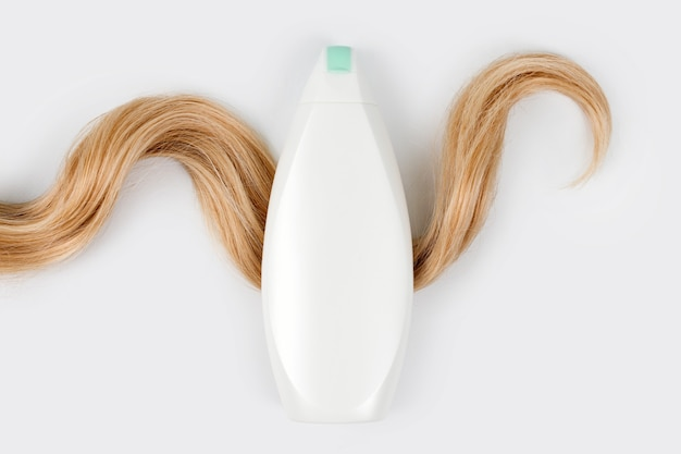 Bottiglia di shampoo o balsamo e ciocca di capelli biondi ricci isolati su sfondo chiaro, vista dall'alto. disposizione piatta, copia spazio per il testo. cosmetici per la cura dei capelli, prodotti di bellezza per la cura dei capelli, trattamento dei capelli.
