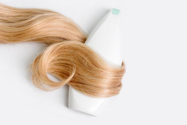 Bottiglia di shampoo o balsamo avvolta in una ciocca di capelli biondi ricci isolati su sfondo chiaro, vista dall'alto. disposizione piatta, copia spazio per il testo. cosmetici per la cura dei capelli, prodotti di bellezza per la cura dei capelli, trattamento dei capelli.