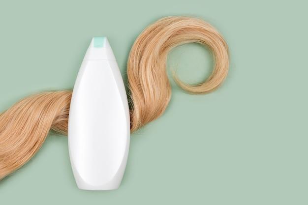 Bottiglia di shampoo o balsamo avvolta in una ciocca di capelli biondi ricci su sfondo menta chiaro, vista dall'alto. piatto disteso in colori pastello, mockup. cosmetici per la cura dei capelli, prodotti di bellezza per la cura dei capelli, trattamento dei capelli