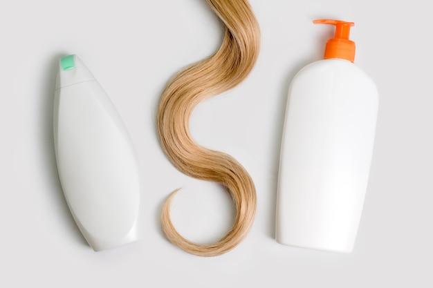 Bottiglie di shampoo e balsamo e ciocca di capelli biondi ricci isolati su sfondo chiaro, vista dall'alto. disposizione piatta, copia spazio per il testo. cosmetici per la cura dei capelli, prodotti di bellezza per la cura dei capelli, trattamento dei capelli.