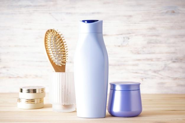 Shampoo, maschera per capelli e spazzola per capelli su uno sfondo di legno.