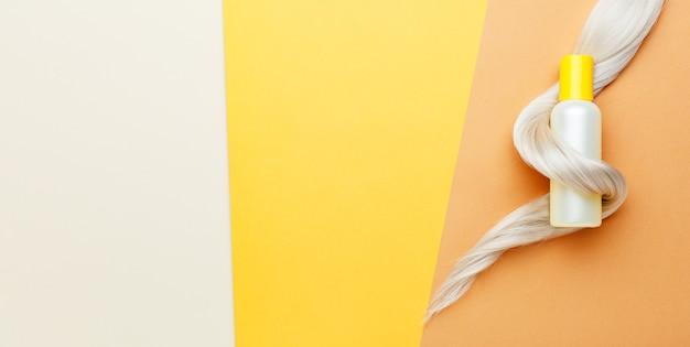 Shampoo flacone arancione con ricciolo di capelli biondi. cosmetici per il trattamento dell'igiene dei capelli. servizi di salone di bellezza, colorazione dei capelli e parrucchiere. web banner lungo vista dall'alto copia spazio sfondo giallo.