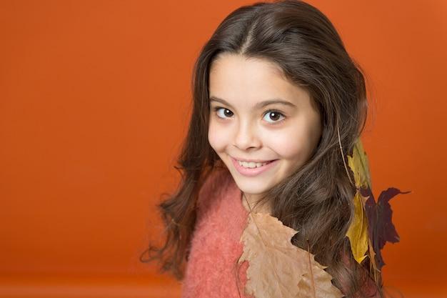 Shampoo che profuma di autunno. la ragazza felice indossa foglie colorate nei capelli lunghi. shampoo ai profumi autunnali. shampoo per capelli normali, secchi o grassi. routine per la cura dei capelli. shampoo per capelli calore autunnale, copia spazio.