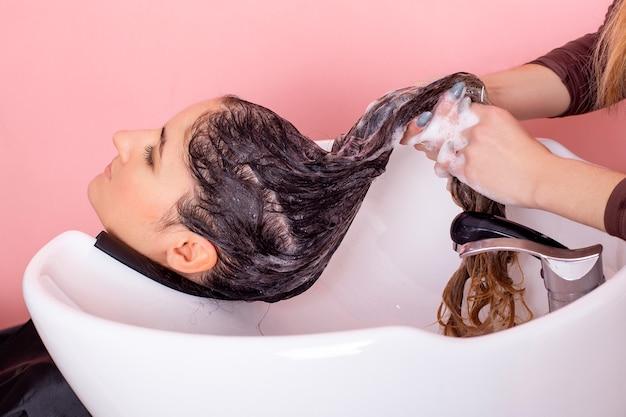 Lavaggio con shampoo di capelli castani femminili