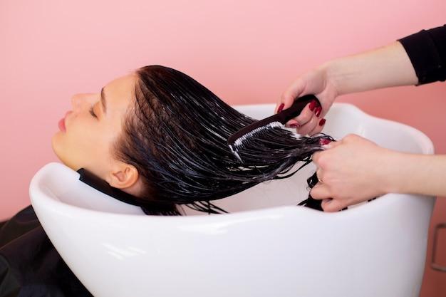 Shampoo lavaggio della testa femminile con lunghi capelli castani nel salone di parrucchiere