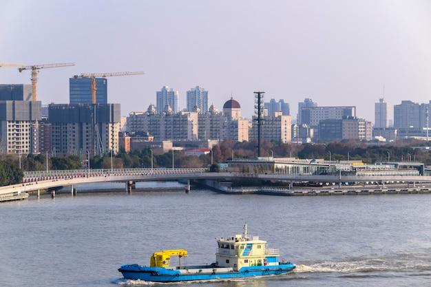 Shanghai, cina - 18 febbraio 2021: il fiume huangpu a shanghai, cina con una nave da carico che trasferisce merci. sullo sfondo i moderni grattacieli del bund.
