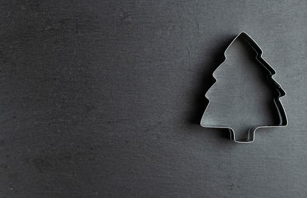 Forma per biscotti sotto forma di un albero di natale su uno sfondo bianco