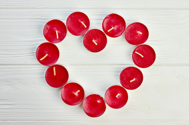 Forma di cuore dalle candele di luce del tè rosso. candele rosse che formano forma di cuore su fondo in legno chiaro, vista dall'alto. concetto di amore e romanticismo.