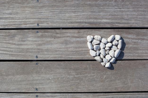 Forma di cuore realizzata con pietre sulle assi di legno dello sfondo del molo love zen life concept