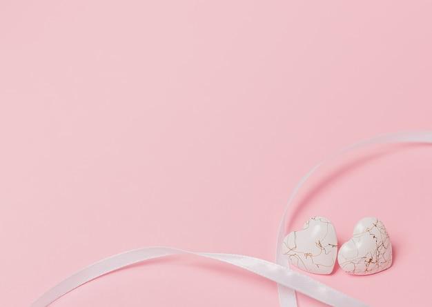 Cuore di forma con nastro wihte su sfondo rosa isolato