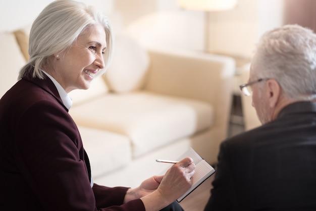 Condividete i punti di vista. allegra imprenditrice invecchiata felice sorridente e seduta in ufficio mentre prende appunti nel taccuino e discute l'argomento con il suo collega