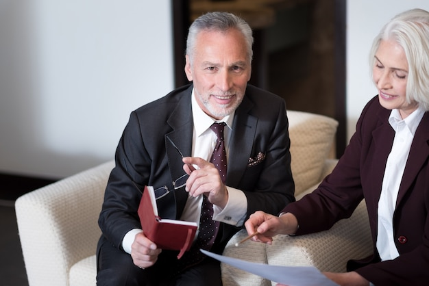 Condividi un'atmosfera positiva. felice imprenditore invecchiato felice sorridente e seduto in ufficio vicino alla donna d'affari mentre si lavora con il suo collega e lo scambio di idee