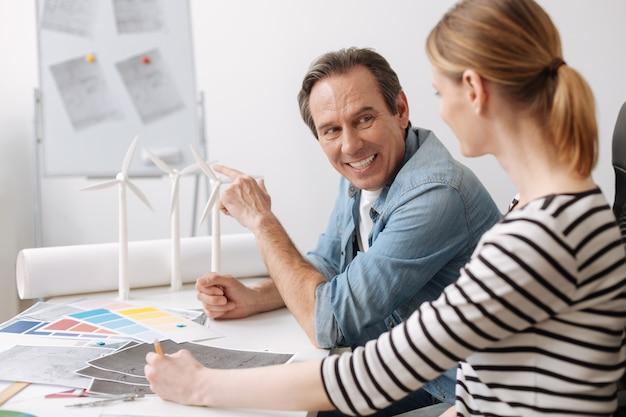 Condividi la tua esperienza. ingegnere professionista felice positivo seduto al tavolo e discutendo con il suo collega più giovane progetto di costruzione di turbine eoliche