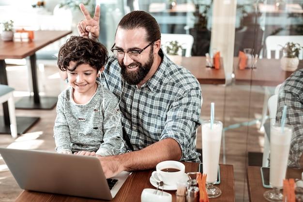 Condivisione degli auricolari. padre e figlio condividono gli auricolari durante la chat video con la madre