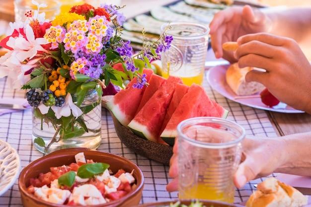Condividere il cibo con la famiglia. popoli caucasici che si godono il brunch o il pasto insieme. frutta e verdura sul tavolo di legno. la luce del sole all'aperto sulla terrazza