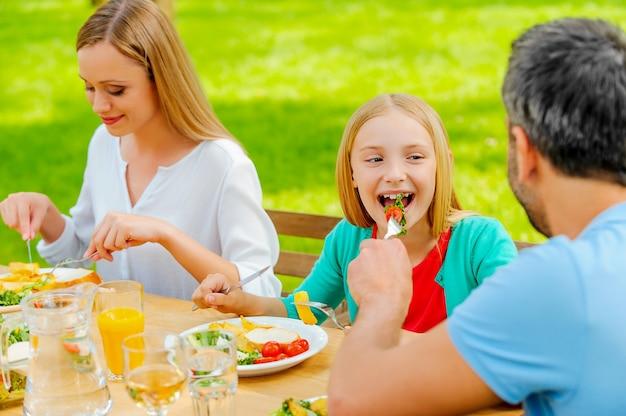 Condividere il cibo con il più vicino. giovane che dà da mangiare a sua figlia con insalata mentre si siede insieme al tavolo da pranzo all'aperto