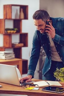 Condivisione di buone notizie. bel giovane che parla al telefono cellulare e guarda il suo laptop mentre si trova vicino alla scrivania in ufficio