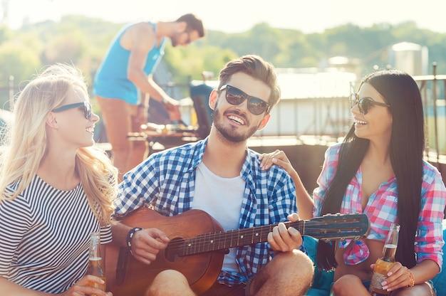 Condividere il buon tempo. tre giovani allegri che si legano l'un l'altro e si siedono sul sacchetto di fagioli con la chitarra mentre l'uomo fa il barbecue in sottofondo