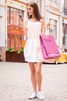 Condividere notizie con gli amici. integrale di bella giovane donna sorridente che tiene le borse della spesa e guarda il suo telefono cellulare mentre sta in piedi all'aperto