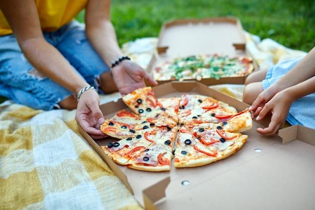 Condivisione della pizza, mani che prendono un pezzo di pizza da una scatola all'aperto, picnic in famiglia, mangiare pizze per cena, consegna di fast food.