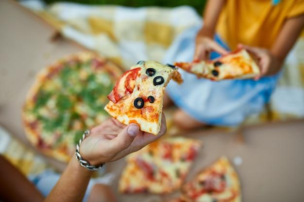 Condivisione della pizza, mani che prendono un pezzo di pizza da una scatola all'aperto,