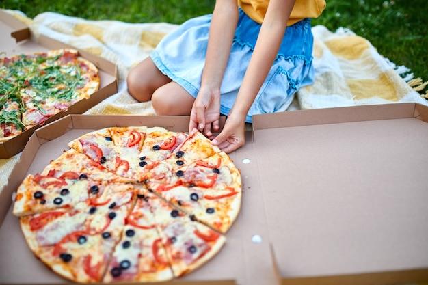 Condividere la pizza, le mani della bambina che prendono un pezzo di pizza da una scatola all'aperto, picnic in famiglia, mangiare pizze per cena, consegna di fast food.