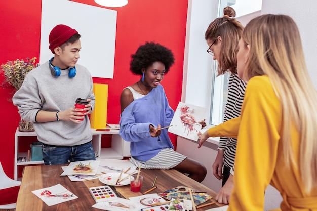 Condivisione del lavoro. studentessa di arte creativa di talento afro-americana che condivide il suo lavoro con un collega
