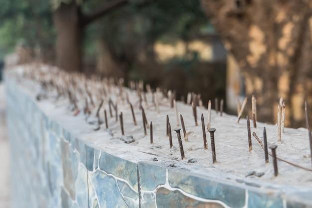 Chiodi affilati di una suite in una recinzione in cemento per la protezione del territorio dalla penetrazione illegale di animali e ladri. sicurezza del sistema e protezione del suolo privato contro l'ingresso illegale