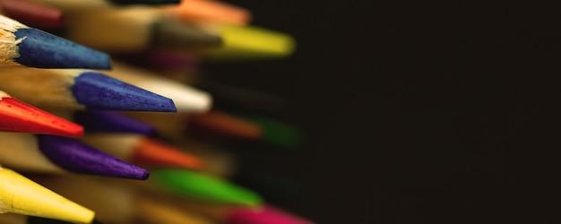 Punte affilate delle matite colorate, foto banner con sfondo nero e spazio copia, primo piano