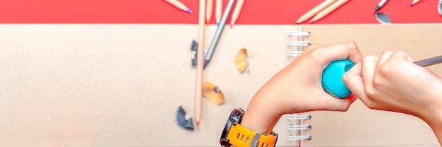 Affila le matite le mani del bambino temperano una matita a scuola durante la lezione sullo sfondo uno schizzo...
