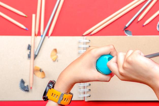 Tempera le matite le mani del bambino temperano una matita a scuola durante la lezione sullo sfondo uno schizzo...