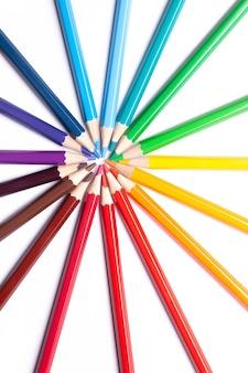 Le matite colorate appuntite si trovano in un cerchio con il naso al centro, materiale scolastico, simbolo lgbt.