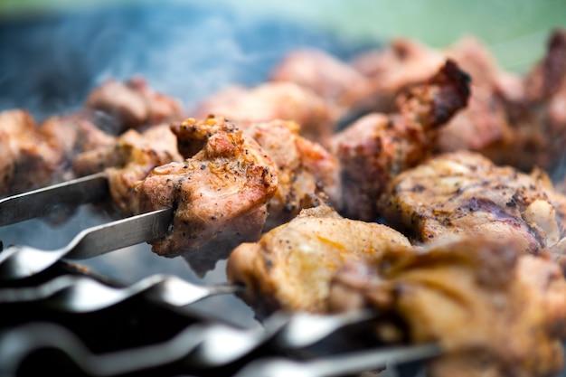 Shashlik o shish kebab che si prepara sulla griglia del barbecue su carbone caldo. pezzi di carne di maiale alla griglia su spiedini di metallo.