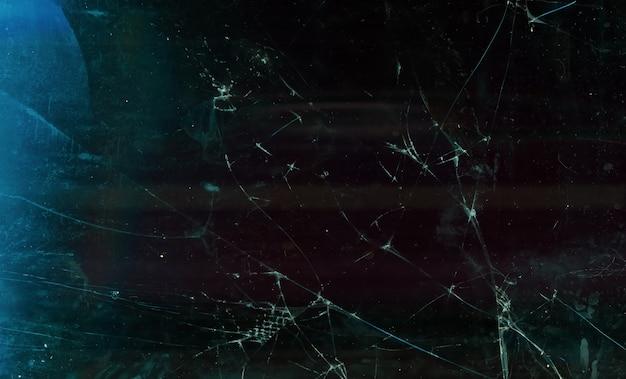 Sfondo in frantumi. vetro rotto sfocato. sfocatura display tablet sporco angosciato congelato scuro con polvere, graffi, impronte digitali, macchie, riflesso lente blu.