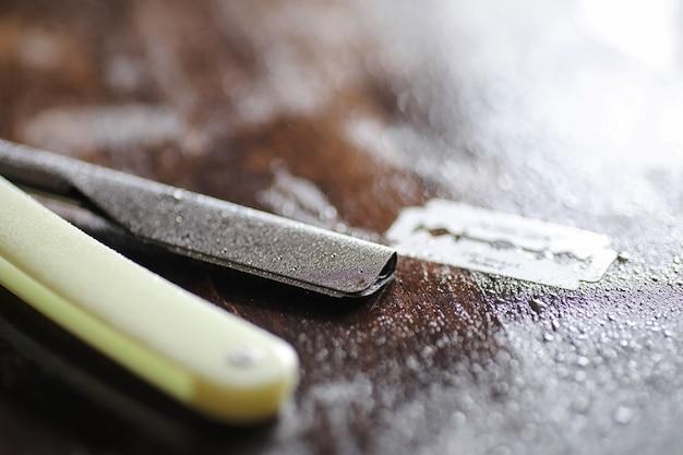 Accessori per la rasatura su uno sfondo in legno e lame usa e getta