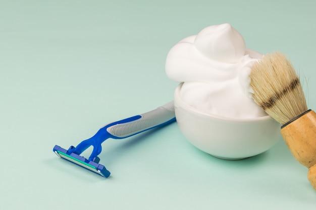 Un pennello da barba in una ciotola con schiuma da barba sulla punta di un rasoio usa e getta. set per la cura del viso di un uomo.