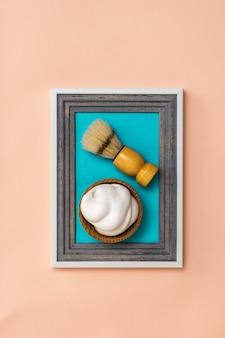 Pennello da barba da barba schiuma da barba nel telaio su uno sfondo di corallo. collage. minimalismo. creatività creativa moderna.